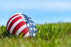 Boule de rugby avec la bannière étoilée sur l'herbe Images libres de droits