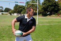 Boule de rugby de lancement de joueur par le poteau de but Photos stock