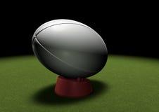 Boule de rugby sur donner un coup de pied la pièce en t sous le projecteur Images stock