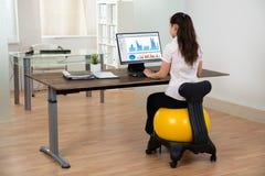 Boule de Sitting On Fitness de femme d'affaires dans le bureau Photo stock