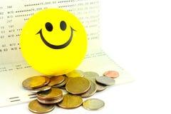 Boule de sourire sur le carnet bancaire avec des pièces de monnaie, bain thaïlandais Images stock