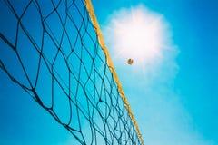 Boule de volleyball au-dessus de filet sur le fond du bleu Images libres de droits