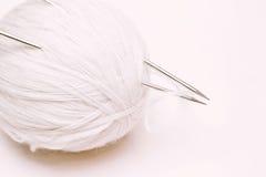 Boule du fil de laine blanc avec des aiguilles de tricotage sur le backgroun blanc Photographie stock