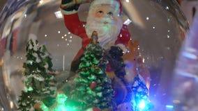 Boule en verre de Noël avec la figure miniature Santa Claus banque de vidéos