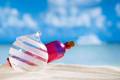 Boule en verre et bouteille de Noël de scintillement sur la plage avec le paysage marin Photos stock