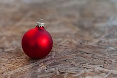 Boule en verre rouge de Noël s'étendant sur le Tableau en bois pendant le matin a Photographie stock libre de droits