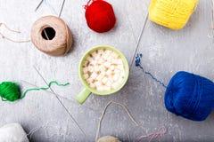 Boule et aiguilles de tricotage multicolores autour de tasse de café verte sur le fond gris Vue supérieure Copiez l'espace Fil à  Photo libre de droits