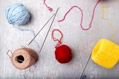 Boule et aiguilles de tricotage multicolores sur le fond gris Vue supérieure Copiez l'espace Fil à tricoter Images stock