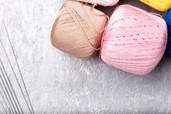 Boule et aiguilles de tricotage multicolores sur le fond gris Vue supérieure Copiez l'espace Fil à tricoter Image libre de droits