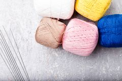 Boule et aiguilles de tricotage multicolores sur le fond gris Vue supérieure Copiez l'espace Fil à tricoter Photos stock