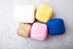 Boule et aiguilles de tricotage multicolores sur le fond gris Vue supérieure Copiez l'espace Fil à tricoter Configuration plate Photos stock