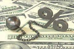 Boule et chaîne de fer de rouille avec le symbole accrochant de pour cent de manchette sur le fond de billets de banque des dolla Images stock