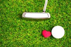 Boule et putter de golf sur le cours vert Photographie stock libre de droits