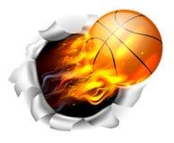 Boule flamboyante de basket-ball déchirant un trou à l'arrière-plan Photo stock