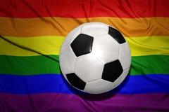 Boule noire et blanche du football sur le drapeau d'homosexuel d'arc-en-ciel Photos stock