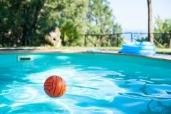 Boule rouge dans une piscine dans le jardin vert Photographie stock