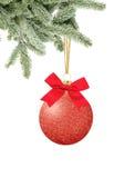 Boule rouge de décor de Noël de scintillement avec l'arc sur le ruban sur l'arbre de neige Images stock