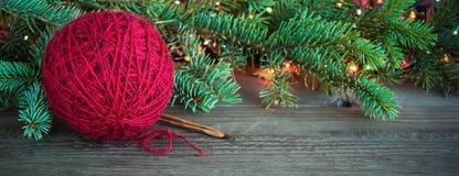Boule rouge de fil de laine et aiguilles de tricotage en bois près d'arbre vert de fourrure de Noël et lumières colorées lumineus image libre de droits