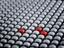 Boule rouge parmi les sphères blanches Photos libres de droits