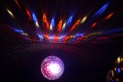 Boule rougeoyante rougeoyante de disco avec des rayons de bleu jaune rouge image libre de droits