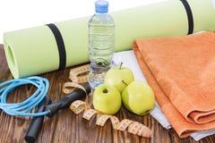 Boule, tapis de yoga et plan rapproché de bouteille d'eau Article de sport, trois pommes vertes et une corde de saut Images stock