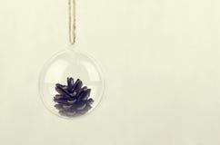 Boule transparente de Noël avec un cône de pin à l'intérieur Photo stock