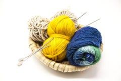 Boule trois des fils de laine, du jaune, du bleu, du beige et des aiguilles de tricotage en acier dans un panier en bois sur un f Photo stock