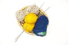 Boule trois des fils de laine, du jaune, du bleu, du beige et des aiguilles de tricotage en acier dans un panier en bois sur un f Photo libre de droits