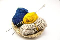 Boule trois des fils de laine, du jaune, du bleu, du beige et des aiguilles de tricotage en acier dans un panier en bois sur un f Photographie stock