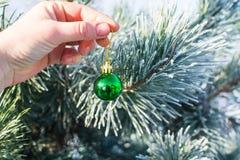 Boule verte de décorations de Noël tenant extérieur disponible Image libre de droits