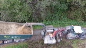Bouledogue aérien avec du bois de chopps de Woodchipper sur le secteur de charge d'un camion banque de vidéos