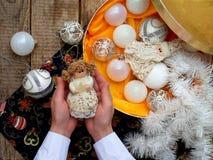 Boules blanches de Noël dans la boîte et fée dans des mains Décoration de Noël Foyer sélectif Photographie stock libre de droits