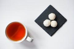 Boules blanches de sucrerie de noix de coco dans des plats de schiste de plat sur le fond en bois rustique avec une tasse de th? photographie stock libre de droits