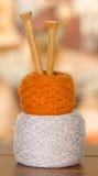 Boules blanches et brunes de fil empilées sur l'un l'autre avec les aiguilles de tricotage en bois se levant de l'intérieur du mi Photographie stock libre de droits