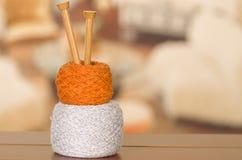 Boules blanches et brunes de fil empilées sur l'un l'autre avec les aiguilles de tricotage en bois se levant de l'intérieur du mi Images stock