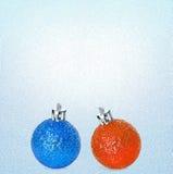 Boules bleues et oranges lumineuses de Noël sur le fond bleu-clair de glace Vous pouvez l'employer en tant que concept de vente d Photographie stock libre de droits