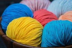 Boules colorées de fil à tricoter dans le panier Photographie stock