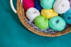 Boules colorées de fil dans le panier sur le fond en bois Image libre de droits