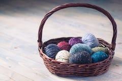 Boules colorées de fil de laine dans un panier sur le fond rustique Photographie stock