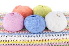 Boules colorées de fil de laine sur le plaid tricoté d'isolement sur le fond blanc Photos libres de droits