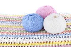 Boules colorées de fil de laine sur le plaid tricoté d'isolement sur le fond blanc Image stock