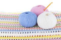 Boules colorées de fil de laine sur le plaid tricoté d'isolement sur le fond blanc Photo libre de droits