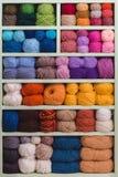 Boules colorées de laine sur des étagères Photos libres de droits