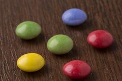 Boules colorées heureuses de chocolat sur le fond en bois Images stock