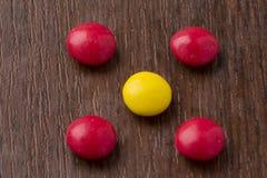 Boules colorées heureuses de chocolat sur le fond en bois Photos libres de droits