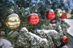 Boules colorées par Noël sur l'arbre dans la neige images stock