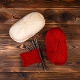 Boules color?es rouges et blanches des aiguilles de fil et de tricotage avec un tricotage sur un fond en bois images libres de droits