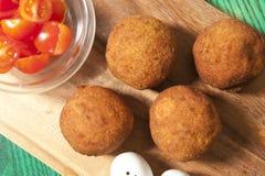 Boules croustillantes de Falafel avec des tomates sur le conseil en bois Image libre de droits