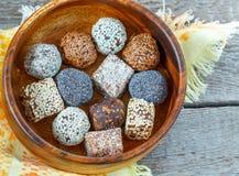 Boules crues saines d'énergie avec du cacao, noix de coco, sésame, chia dans une cuvette en bois Photographie stock libre de droits
