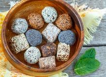 Boules crues saines d'énergie avec du cacao, noix de coco, sésame, chia dans une cuvette en bois Photographie stock